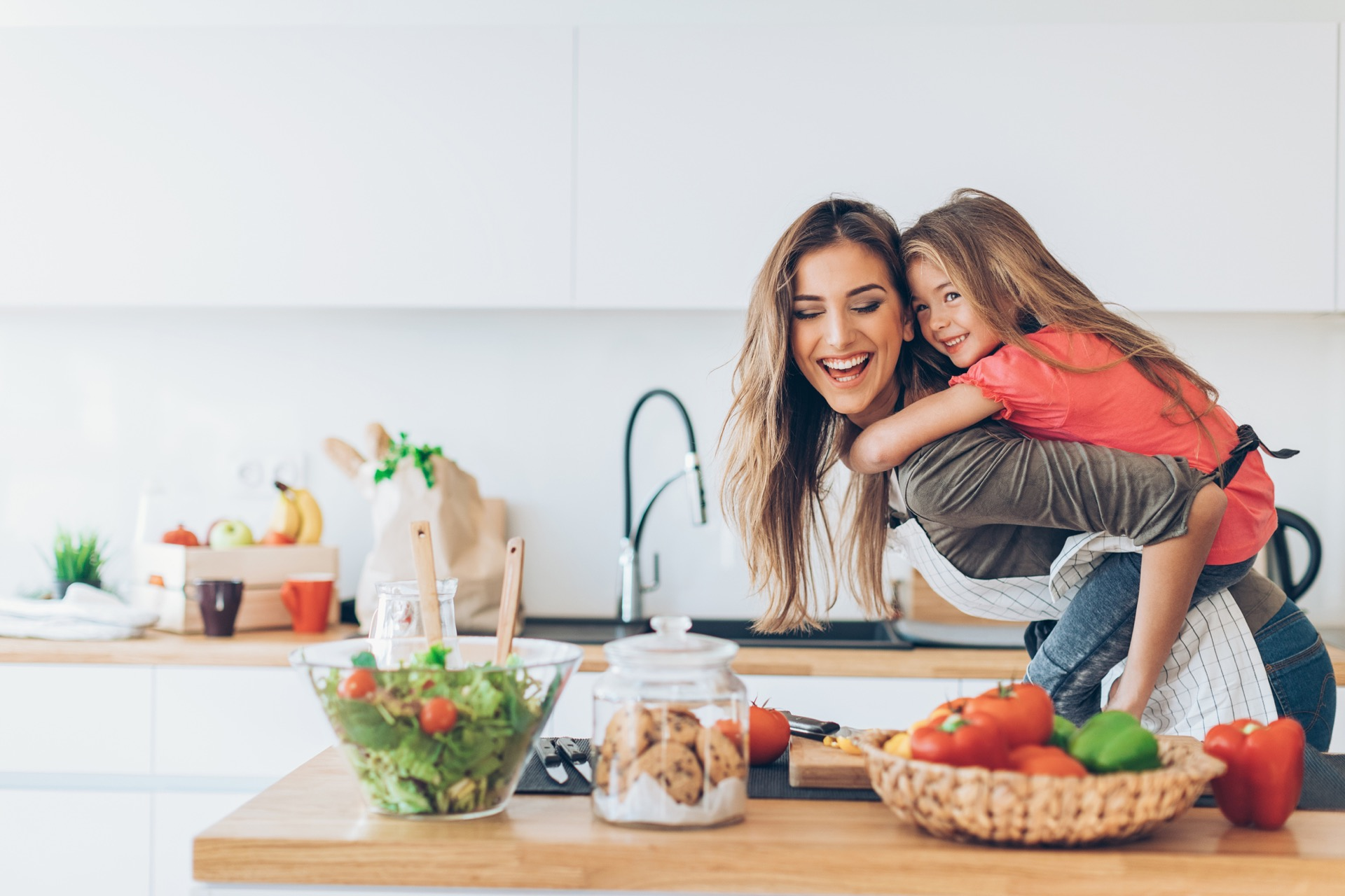 Beautiful mother and daughter having fun piggy-back ride in the kitchen.