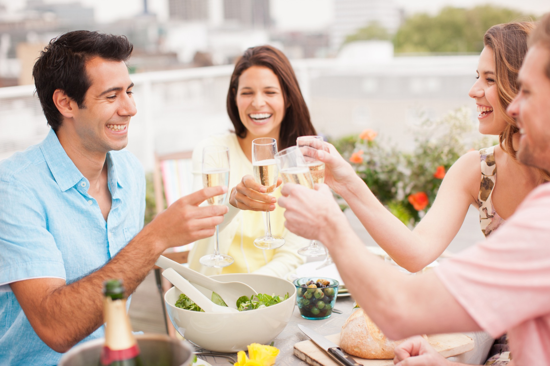 Laughing couples toasting with Champagne outdoors at their downtown Baltimore apartments