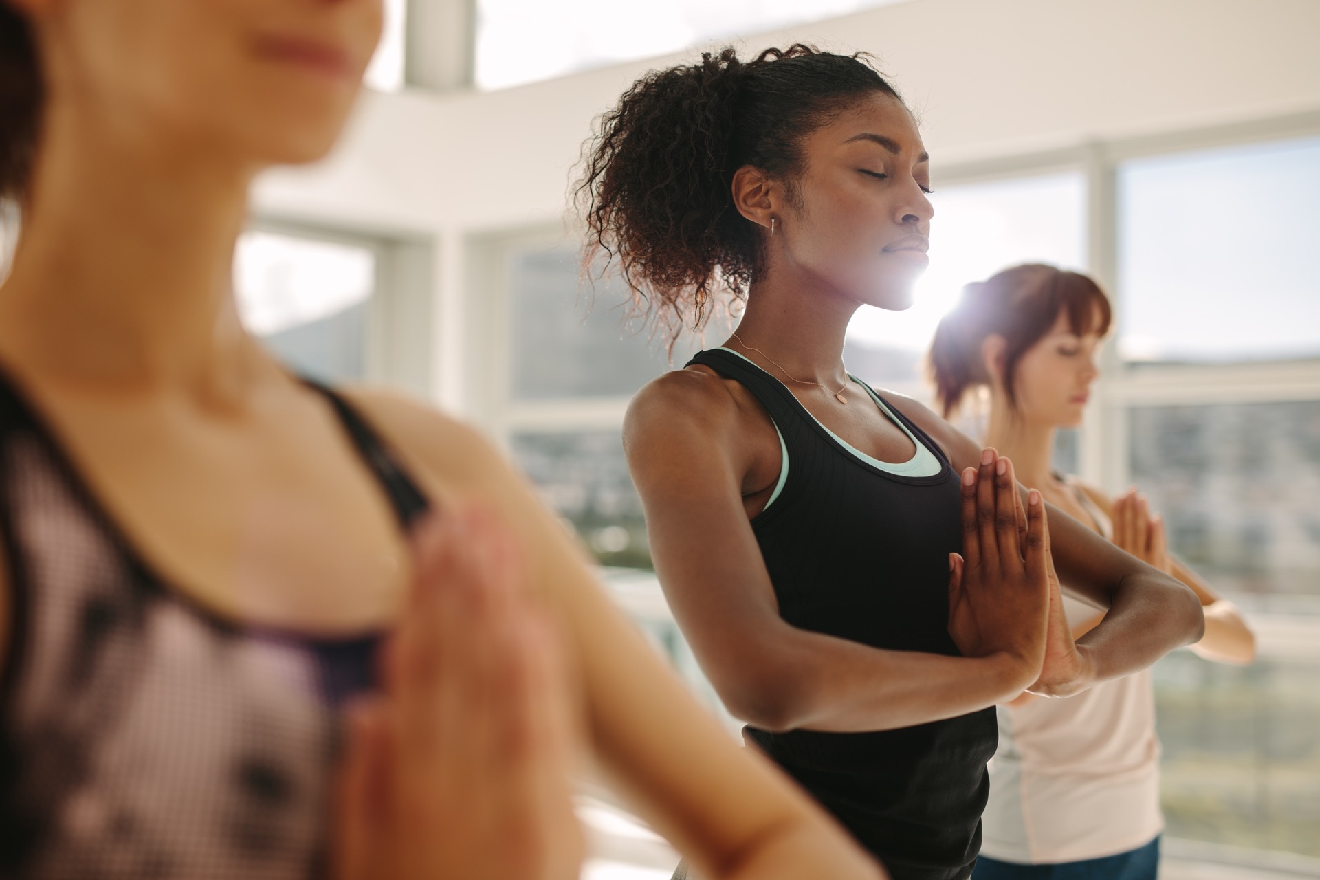 Fit young woman practice yoga with friends. Fitness female doing yoga meditation indoors in the gym at Cirro apartments in downtown Baltimore